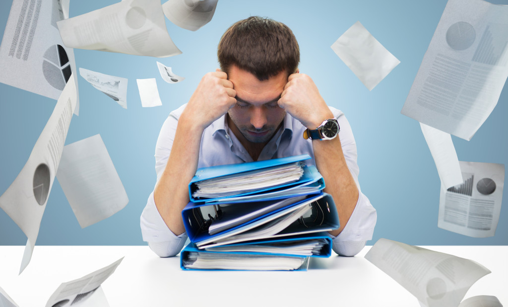 sad businessman with stack of folders at office